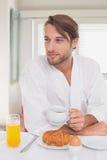 Όμορφο άτομο που έχει το πρόγευμα στον καφέ κατανάλωσης μπουρνουζιών του στοκ φωτογραφία