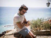 Όμορφο άτομο που ακούει τη μουσική στα ακουστικά υπαίθρια στοκ φωτογραφίες