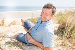 όμορφο άτομο που βρίσκεται στην άμμο κοντά στους αμμόλοφους διακοπών παραλιών Στοκ Φωτογραφίες