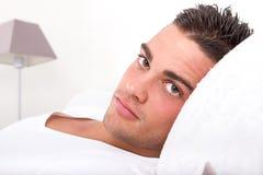 Όμορφο άτομο που βρίσκεται στο κρεβάτι Στοκ Φωτογραφία