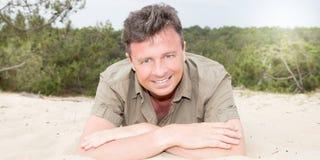 Όμορφο άτομο που βρίσκεται τη θερινή ημέρα παραλιών άμμου Στοκ Φωτογραφία