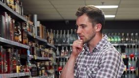 Όμορφο άτομο που εξετάζει τα ποτά για την πώληση στην υπεραγορά απόθεμα βίντεο