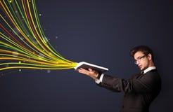 Όμορφο άτομο που διαβάζει ένα βιβλίο ενώ οι ζωηρόχρωμες γραμμές βγαίνουν Στοκ Φωτογραφίες