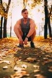 Όμορφο άτομο που κάθεται οκλαδόν στο πάρκο φθινοπώρου sportswear στοκ εικόνες