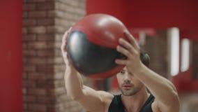 Όμορφο άτομο που κάνει την κοντόχοντρη άσκηση με τη σφαίρα στη λέσχη ικανότητας απόθεμα βίντεο