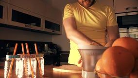 Όμορφο άτομο που κατασκευάζει το φρέσκο χυμό από πορτοκάλι με ένα juicer στο σπίτι απόθεμα βίντεο