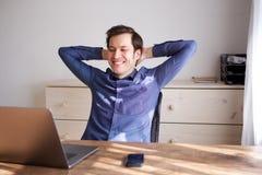 Όμορφο άτομο που κλίνει πίσω στην καρέκλα με το lap-top και το τηλέφωνο Στοκ φωτογραφία με δικαίωμα ελεύθερης χρήσης