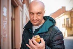 Όμορφο άτομο που κρατά ένα κέικ στα χέρια του στοκ φωτογραφία