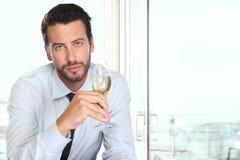 Όμορφο άτομο που πίνει ένα γυαλί του λευκού κρασιού σπινθηρίσματος, στο φραγμό Στοκ φωτογραφία με δικαίωμα ελεύθερης χρήσης