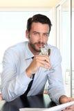 Όμορφο άτομο που πίνει ένα γυαλί του λευκού κρασιού σπινθηρίσματος, κάθισμα α Στοκ Φωτογραφίες