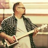Όμορφο άτομο που παίζει την κιθάρα κιβωτίων πούρων του Στοκ Φωτογραφία