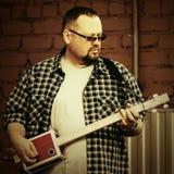 Όμορφο άτομο που παίζει την κιθάρα κιβωτίων πούρων του Στοκ Εικόνες