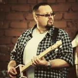 Όμορφο άτομο που παίζει την κιθάρα κιβωτίων πούρων του Στοκ εικόνα με δικαίωμα ελεύθερης χρήσης