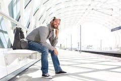 Όμορφο άτομο που περιμένει στην πλατφόρμα τραίνων με το τηλέφωνο Στοκ Εικόνες