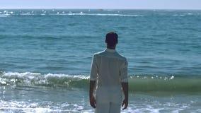 Όμορφο άτομο που περπατά προς τη θάλασσα απόθεμα βίντεο