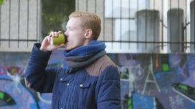 Όμορφο άτομο που περπατά στην οδό και που κοιτάζει κατά μέρος κρατώντας το φλιτζάνι του καφέ απόθεμα βίντεο