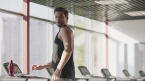 Όμορφο άτομο που περπατά treadmill στη μηχανή στη λέσχη ικανότητας φιλμ μικρού μήκους