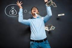 Όμορφο άτομο που στέκεται πέρα από τον πίνακα με τη συρμένη έννοια δολαρίων στοκ εικόνες