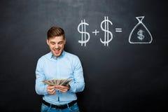 Όμορφο άτομο που στέκεται πέρα από τον πίνακα με τη συρμένη έννοια δολαρίων Στοκ Φωτογραφία