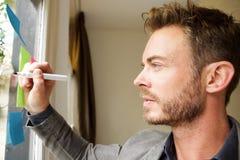 Όμορφο άτομο που στέκεται στο γραφείο που γράφει στον πίνακα ιδέας Στοκ φωτογραφία με δικαίωμα ελεύθερης χρήσης