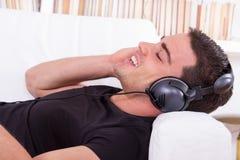 Όμορφο άτομο που στηρίζεται στον καναπέ που ακούει τη μουσική με τα ακουστικά στοκ εικόνες με δικαίωμα ελεύθερης χρήσης