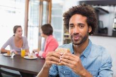 Όμορφο άτομο που τρώει ένα σάντουιτς στοκ φωτογραφία με δικαίωμα ελεύθερης χρήσης