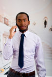 Όμορφο άτομο που φορούν το πουκάμισο και δεσμός που στέκεται στην περιοχή λόμπι που μιλά στο κινητό τηλέφωνο, επιχειρησιακή έννοι στοκ εικόνες