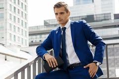 Όμορφο άτομο σε ένα μπλε κοστούμι σε ένα κλίμα πόλεων μια ηλιόλουστη ημέρα Στοκ Φωτογραφίες