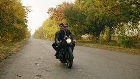Όμορφο άτομο στα γυαλιά ηλίου που κάθονται με τη φίλη του πίσω από τη ρόδα μιας μοτοσικλέτας και που οδηγούν στο δρόμο ασφάλτου απόθεμα βίντεο