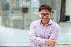 Όμορφο άτομο στα γυαλιά που στέκονται με τα όπλα που διασχίζονται υπαίθρια και που χαμογελούν Στοκ Φωτογραφία