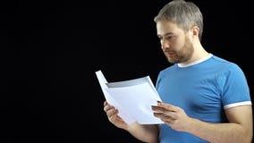 Όμορφο άτομο στην μπλε μπλούζα που κοιτάζει μέσω των εγγράφων Cotract, λογαριασμοί, έννοιες επιστολών Μαύρη ανασκόπηση στοκ εικόνες με δικαίωμα ελεύθερης χρήσης