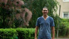Όμορφο άτομο στη βροχή που στέκεται υπαίθρια τη κάμερα και το χαμόγελο απόθεμα βίντεο