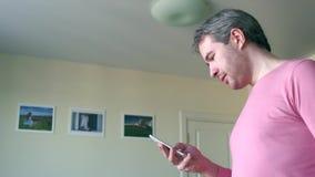 Όμορφο άτομο στη ρόδινη μπλούζα που τυλίγει app στο smartphone του στο σπίτι Στοκ Εικόνες