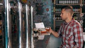Όμορφο άτομο στις διαφορετικές μπύρες Degustating μπύρας κατανάλωσης μπαρ Αγγλική μπύρα και αχθοφόρος δυνατής μπύρας στον καφέ απόθεμα βίντεο