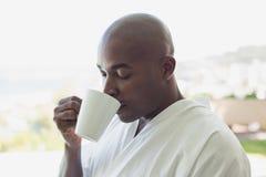Όμορφο άτομο στον καφέ κατανάλωσης μπουρνουζιών έξω Στοκ Εικόνα
