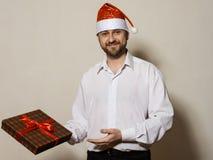 Όμορφο άτομο στο κιβώτιο δώρων εκμετάλλευσης Χριστουγέννων ΚΑΠ Στοκ φωτογραφία με δικαίωμα ελεύθερης χρήσης