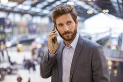 Όμορφο άτομο στο κινητό τηλέφωνο στο σταθμό αιθουσών Στοκ Φωτογραφίες