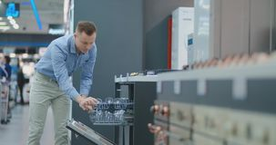 Όμορφο άτομο στο πουκάμισο για να ανοίξει την πόρτα των συσκευών πλυντηρίων πιάτων στο κατάστημα και να συγκρίνει με άλλα πρότυπα απόθεμα βίντεο