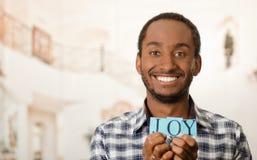 Όμορφο άτομο Headshot που κρατά ψηλά τα μικρά γράμματα που συλλαβίζουν τη χαρά λέξης και που χαμογελούν στη κάμερα Στοκ φωτογραφίες με δικαίωμα ελεύθερης χρήσης