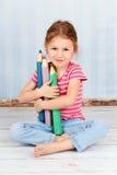 Όμορφο έξυπνο προσχολικό κορίτσι που κρατά τα μεγάλα κραγιόνια Στοκ φωτογραφία με δικαίωμα ελεύθερης χρήσης