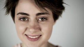 Όμορφο έφηβη ή νέα γυναίκα που χαμογελά και που αναβοσβήνει, γκρίζο υπόβαθρο απόθεμα βίντεο