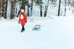 Όμορφο έφηβη σε ένα μακρύ κόκκινο κάτω άσπρο καπέλο σακακιών και ένα μαντίλι που έχουν τη διασκέδαση έξω σε ένα ξύλο με το χιόνι  στοκ φωτογραφία με δικαίωμα ελεύθερης χρήσης