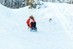 Όμορφο έφηβη σε ένα μακρύ κόκκινο κάτω άσπρο καπέλο σακακιών και ένα μαντίλι που έχουν τη διασκέδαση έξω σε ένα ξύλο με το χιόνι  στοκ εικόνες