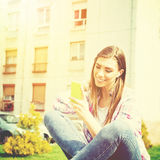 Όμορφο έφηβη στο πάρκο με το έξυπνο τηλέφωνο που ακούει τη μουσική Στοκ Φωτογραφία