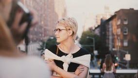Όμορφο ήρεμο καυκάσιο ξανθό κορίτσι με την κοντή τρίχα eyeglasses που εξετάζει μακριά το photoshoot έξω, που θέτει στη κάμερα φιλμ μικρού μήκους