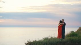 Όμορφο αγαπώντας ζεύγος στην άκρη του απότομου βράχου που εξετάζει το ηλιοβασίλεμα φιλμ μικρού μήκους