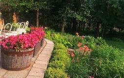 Όμορφο αγγλικό patio κήπων με τους κρίνους και ρόδινο πορτοκαλή πράσινο πετρών Στοκ φωτογραφία με δικαίωμα ελεύθερης χρήσης