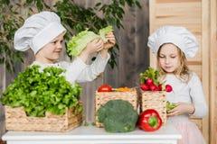 Όμορφο αγόρι και όμορφο παιχνίδι νέων κοριτσιών στους αρχιμάγειρες κουζινών τρόφιμα υγιή Λαχανικά στοκ εικόνες