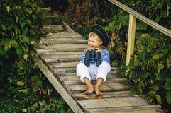Όμορφο αγόρι στην ΚΑΠ και τις διόπτρες του που θέτουν τη συνεδρίαση σε μια ξύλινη γέφυρα Στοκ φωτογραφία με δικαίωμα ελεύθερης χρήσης