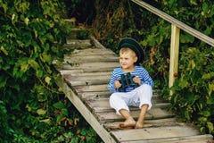 Όμορφο αγόρι στην ΚΑΠ και τις διόπτρες του που θέτουν τη συνεδρίαση σε μια ξύλινη γέφυρα Στοκ φωτογραφίες με δικαίωμα ελεύθερης χρήσης